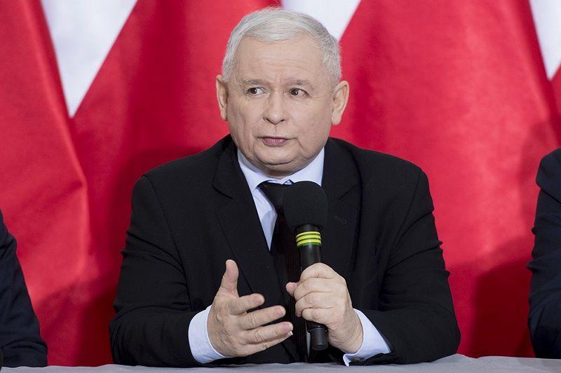 Prezes PiS Jarosław Kaczyński z mikrofonem na tle polskich flag, źródło pis.org.pl