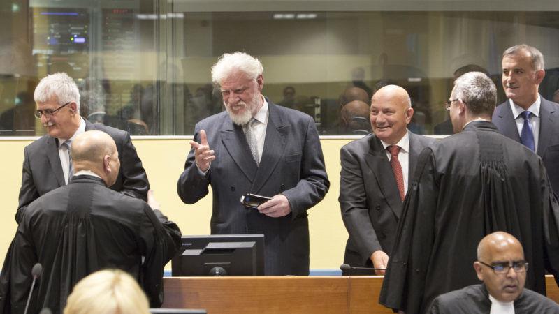 Slobodan Praljak (z siwą brodą) na sali sądowej w Hadze, źródło Wikipedia