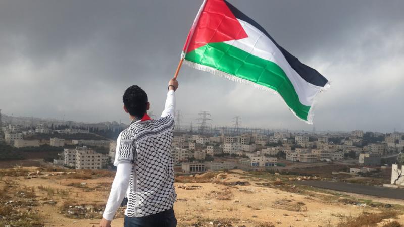 Mężczyzna powiewający palestyńską flagą, źródło Wikipedia