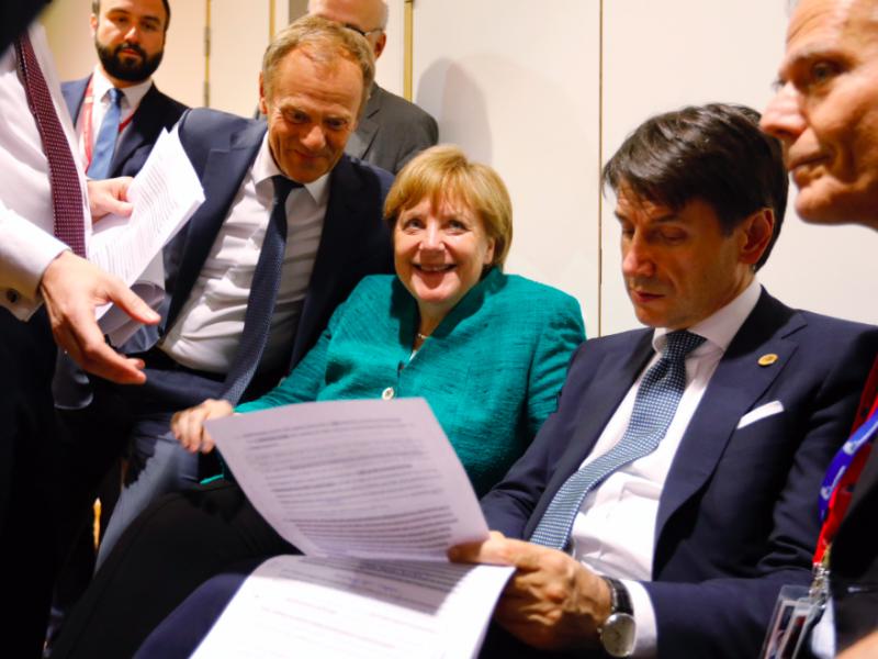 Przewodniczący Rady Europejskiej Donald Tusk, kanclerz Niemiec Angela Merkel i premier Włoch Giuseppe Conte nad roboczym tekstem konkluzji ze szczytu UE, źródło: European Council