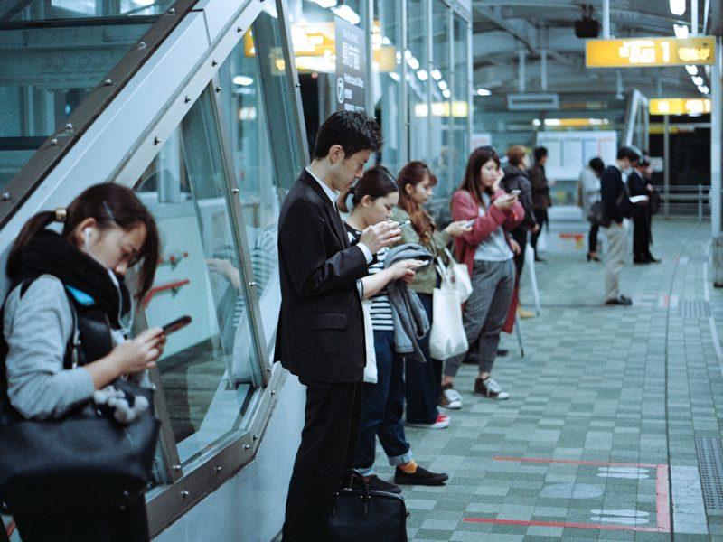 Ludzie stojący na przystanku [Unsplash]