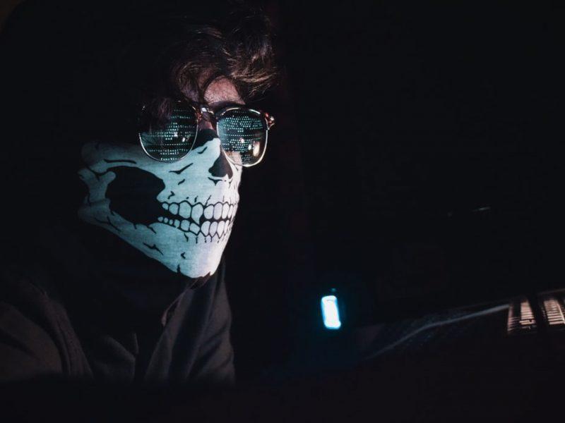 Mężczyzna siedzący w masce przed komputerem [Unsplash]