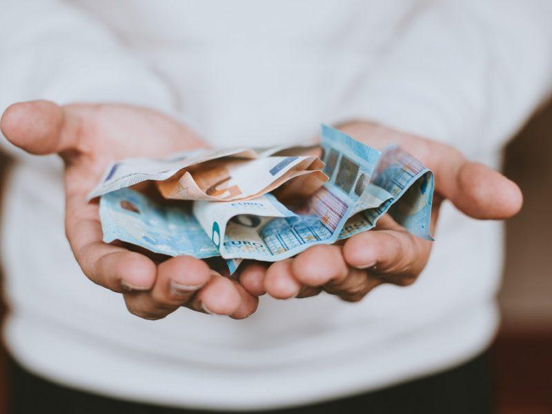 Osoba trzymająca pieniądze [Unsplash]