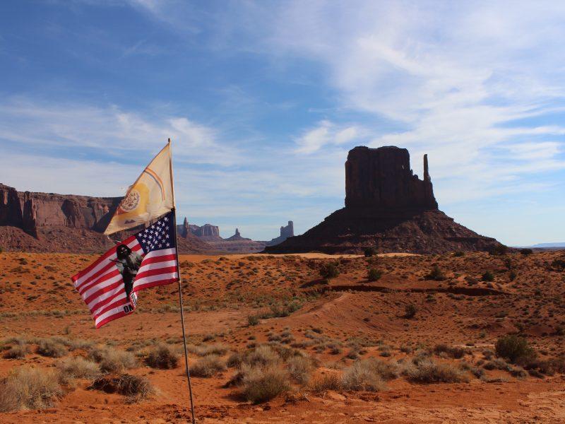 Flaga Narodu Navaho i flaga amerykańska. Monument Valley Navajo Tribal Park. Fot. Chloé Stein on Unsplash