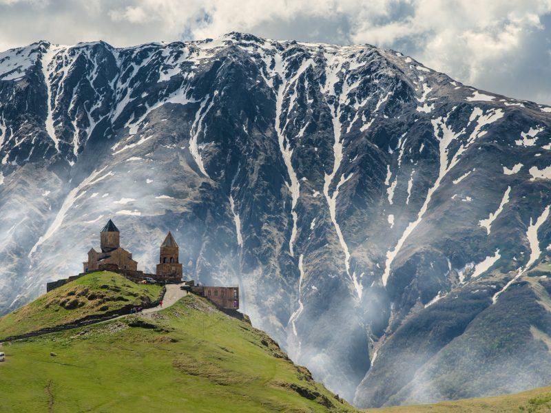 Położony w górach i oferujący wspaniały widok na Pasmo Boczne Wielkiego Kaukazu kościół Świętej Trójcy (Cminda Sameba) nieopodal miasteczka Stepancminda (dawne Kazbegi) to jednak z największych atrakcji turystycznych północnej Gruzji (Photo by Iman Gozal on Unsplash)