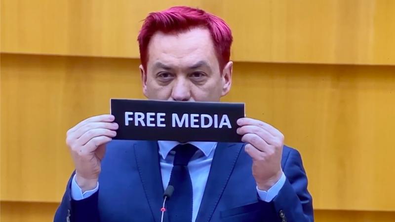 """Robert Biedroń, który wypowiedział słowa """"tak wyglądałaby demokracja bez wolnych mediów"""", po czym przestał mówić i przez chwilę stał na mównicy z kartką z napisem """"Free Media"""" (""""Wolne Media"""")"""