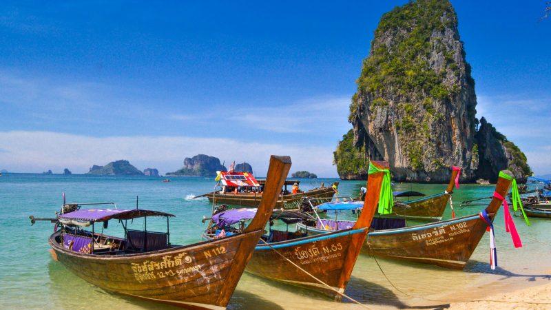 Łodzie wycieczkowe na jednej plaż na tajlandzkiej wyspie Phuket (Photo by Sumit Chinchane on Unsplash)